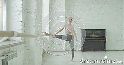 Hübscher Tänzer, der am Barre im Ballettstudio aufwärmt stock video