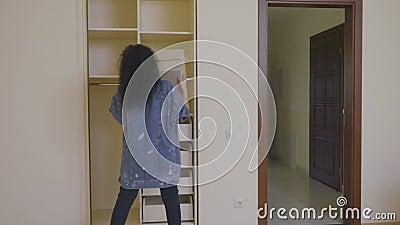 Hübsches Mädchen setzte einen Kasten mit Sachen in eine leere Garderobe in einem neuen Haus ein stock video footage