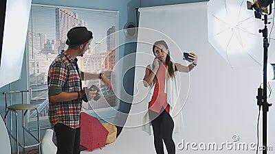 Hübsches schwarzes Modell, das sich auf Smartphone beim Fotoshooting in einem modernen Studio selber macht stock footage