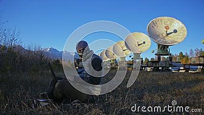 Hacker hackea el radiotelescopio utilizando un portátil Hombre para programar hackeo de laptop por naturaleza El terrorista se es metrajes