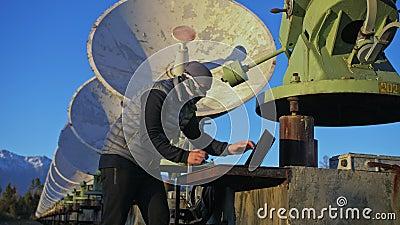 Hacker hackea el radiotelescopio utilizando un portátil Hombre para programar hackeo de laptop por naturaleza El terrorista se es almacen de video