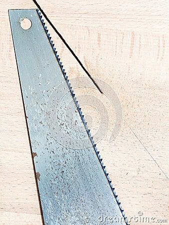 Hacksaw at wooden board