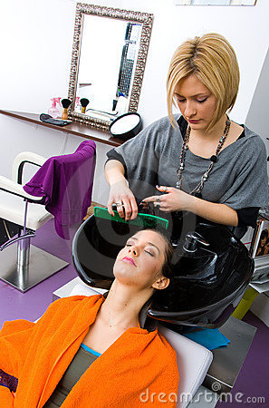 Hair stylist washing woman hair