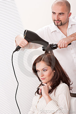 Hairdresser with hair dryer at salon with customer
