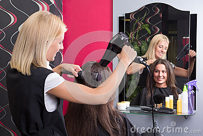 Hairdresser with hairdryer and hairbrush drying female hair in s