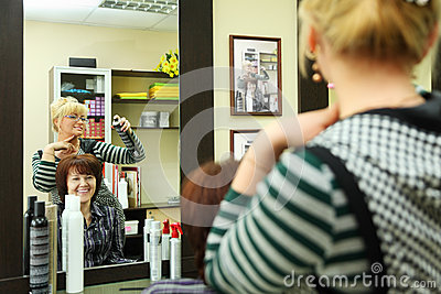 Hairdresser makes hair styling for woman