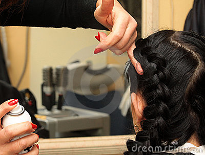 Hairdresser makes hairstyle on long black hair