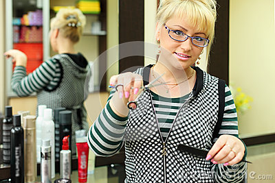 Hairdresser with scissors and comb in workplace