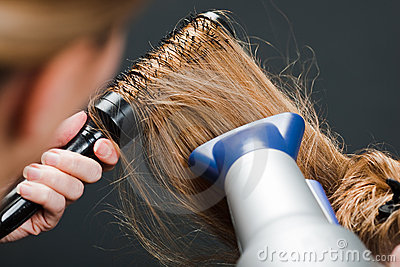 Hairdresser using hairbrush and hair-dryer