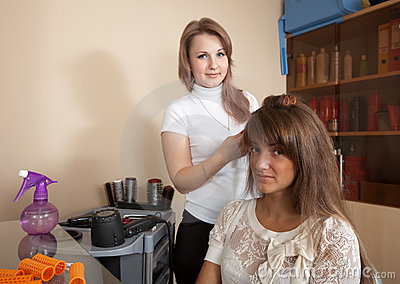 Hairdresser works on woman hair