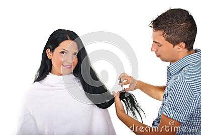 Hairstylist cutting long woman hair