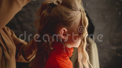 Hairstylist making hairstyle with curly hair for young fashion model in beauty studio. Beauty stylist touching blond. Hair after curling. Young girl receiving stock footage