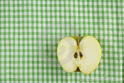 A half of apple on tablecloth