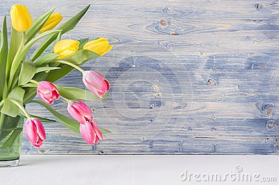 Half bouquet red and yellow tulips in green glass vase on blue shabby wooden background with copy space. Spring easter home decor. Stock Photo