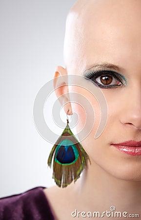 Half face studio portrait of hairless woman