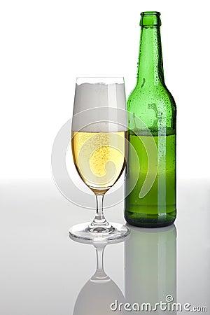 Half full glass of beer and bottle