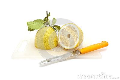 Half Japanese lemon on cutting board with knife, isolated