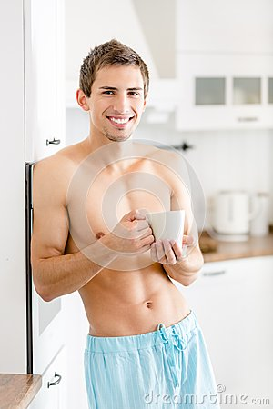 Half-naked male with cup of tea at kitchen