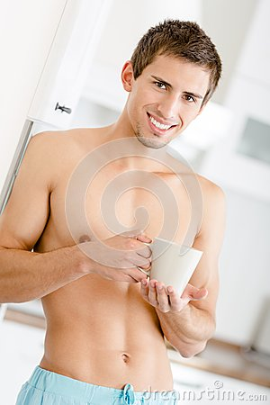 Half-naked man with cup of tea at kitchen