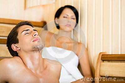 Half-naked man and girl relaxing in sauna