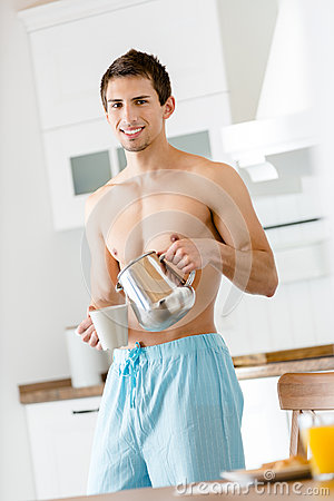 Half-naked man pouring tea at the kitchen