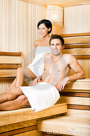 Half-naked man and woman relaxing in sauna
