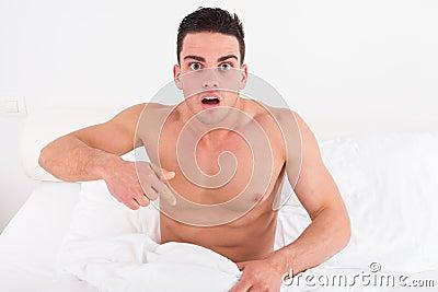 Half naked young man in bed  looking down at his underwear at hi