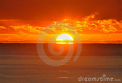 A half sun shows over ocean at sunrise