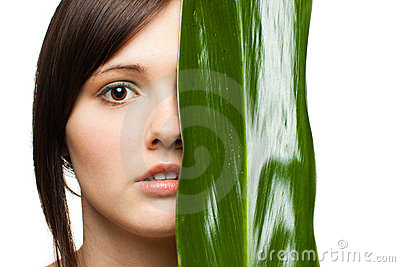 Half of woman s face with green leaf