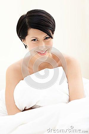Halfnaked Frau umarmt die Decke