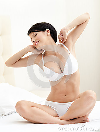 Halfnaked woman stretches herself on the bed