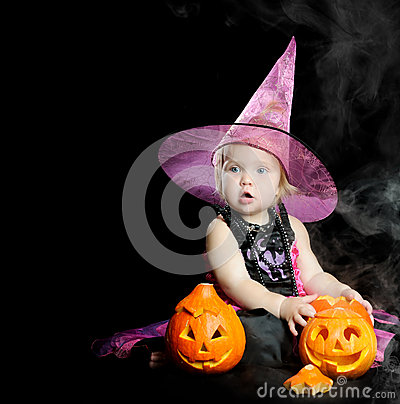 Halloween baby witch with a carved pumpkin