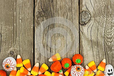 Halloween candy bottom border against rustic wood Stock Photo