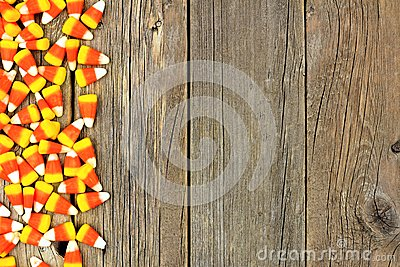 Halloween candy corn side border over old wood Stock Photo