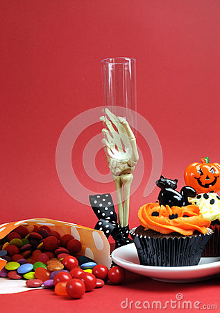 Halloween cupcakes, skeleton glass and candy treats on red background - vertical.