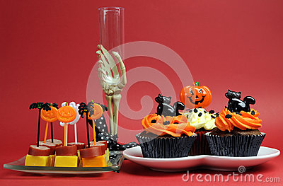 Halloween party food with skeleton hand glass on red background.