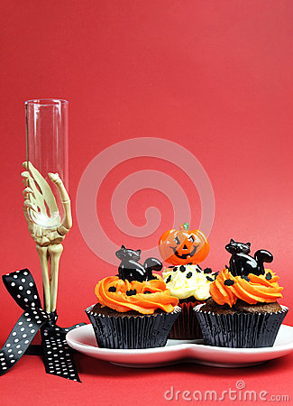 Halloween party food with skeleton hand glass on red background - vertical with copyspace.