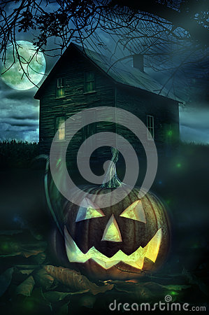 Halloween pumpkin in front of a Spooky house