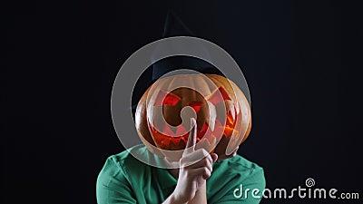 Halloween. Pumpkin head showing gesture of silence. stock footage
