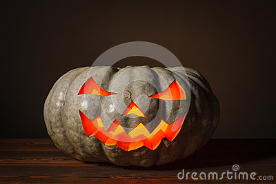 Halloween pumpkin standing on the wooden table