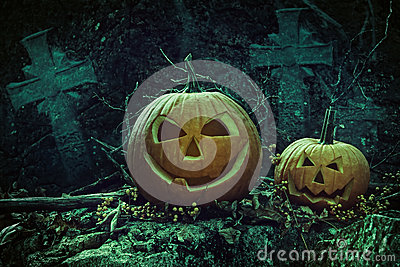 Halloween pumpkins in graveyard at night