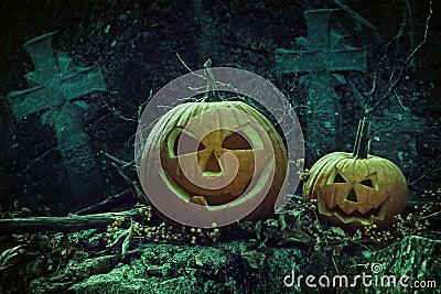 Halloween pumpkins in graveyard at night