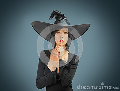 Halloween witch makes silence gesture