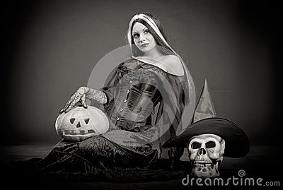 Halloween witch with a skull and pumpkin