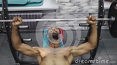 Halterofilista que faz a imprensa com o barbell no gym video estoque