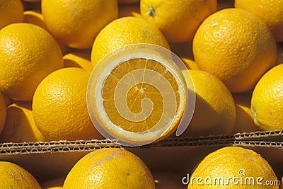 A halved orange rests on oranges in boxes
