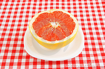 Halved red grapefruit on tablecloth