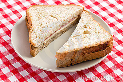 Ham sandwich on checkered tablecloth