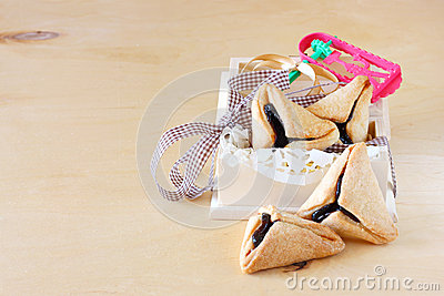 Hamantaschen cookies or hamans ears and Noisemaker for Purim celebration in wooden box