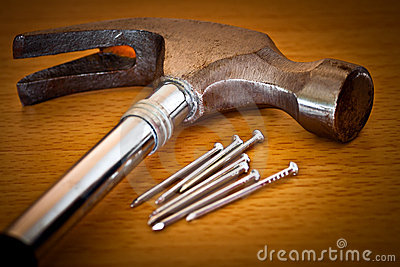 Hammer and nails on a wood background